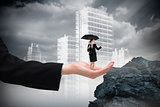 Composite image of young businesswoman holding umbrella in hand