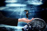 Composite image of young businesswoman holding umbrella in large hand