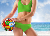Composite image of fit girl in green bikini holding flag ball