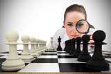 Composite image of thinking businesswoman with magnifying glass