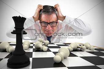 Composite image of stressed businessman touching his head