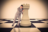 Composite image of portrait of a handsome businessman pushing chess piece