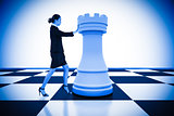 Composite image of businesswoman pushing chess piece