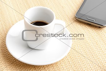 dark espresso in a cup near smartphone