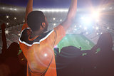 Composite image of cheering football fan in orange jersey