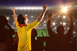 Composite image of cheering football fan in yellow jersey