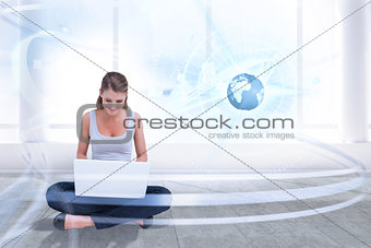 Composite image of cross legged woman using a laptop