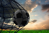 Composite image of football in back of the net