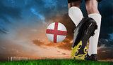 Composite image of football boot kicking england ball