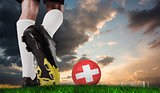 Composite image of football boot kicking swiss ball