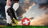 Composite image of football boot kicking swiss ball
