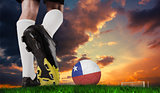 Composite image of football boot kicking chile ball