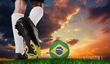 Composite image of football boot kicking brazil ball