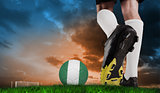 Composite image of football boot kicking nigeria ball