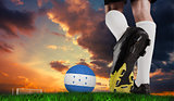 Composite image of football boot kicking honduras ball