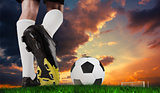 Composite image of football boot kicking ball