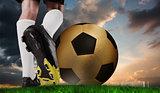 Composite image of football boot kicking huge gold ball