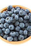 Blueberries in a wooden bowl closeup.