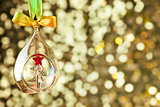 Christmas magic golden background with glass bauble and colorful