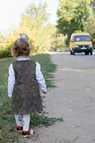 little girl waits for the bus