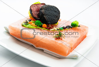 Grilled barbecue steaks on a crystal salt cooking board