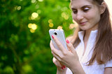 Young Beautiful Woman Using her Smart Phone Outdoor