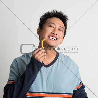 Asian male shaving his beard