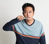 Asian guy brushing teeth