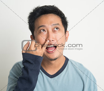 Asian man picking nose
