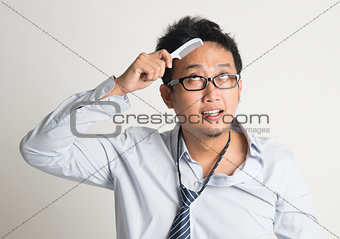 Asian businessman combing hair