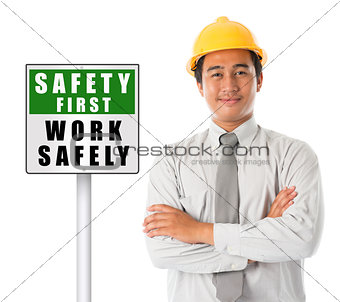 Asian male wearing yellow hardhat with safety first sign board.