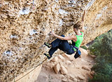 Young female rock climber on a face of a cliff