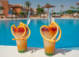 Two fruit cocktails by pool