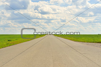 Green grass, road and clouds