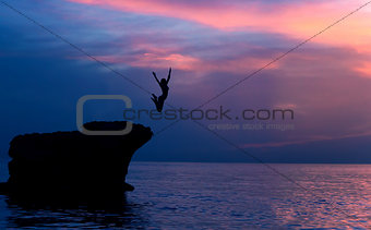 Brave girl jumping from rocks