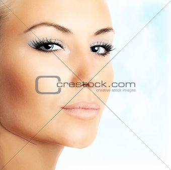 Beautiful female face over abstract blue sky background