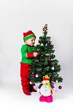 Baby boy dressed as Santa's Helper decorating  Christmas tree.