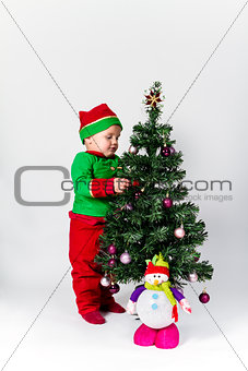 Baby boy dressed as Santa's Helper decorating  Christmas tree.