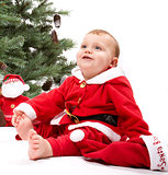 Santa Baby boy sitting next to Christmas tree.
