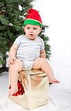 Baby boy sitting on Christmas gift.