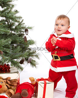 Santa Baby boy standing next to Christmas tree.