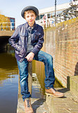 Cute teenage boy in hat (full-length portrait) against canal bac