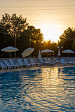Swimming pool in the rays of the setting sun