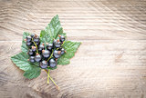 Fresh blackcurrant on leaves on the wooden board