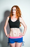 Studio fashion shot: seductive ginger woman wearing shorts and shirt
