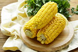fresh boiled cob corn on a wooden plate