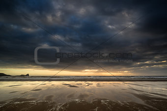Dramatic stormy sky landscape reflected in low tide water on Rho