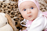 surprised baby in a cap with a soft toy