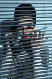 sexy spy woman behind shutters