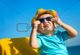 Boy kid in sun glasses and hat on beach
